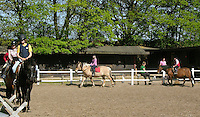 Mädchen beim Reitunterricht auf Ponyhof, Mädchen reiten im Schritt-Tempo auf ihren Reitponys auf dem Reitplatz, Reiten, Reiterhof, Gestüt