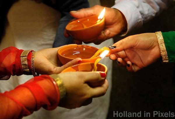 Nederland  Amsterdam. Divali viering in de Shri Guru Nanak Gurdwara Sahib. Mensen steken kaarsjes aan.   Foto Berlinda van Dam / Hollandse Hoogte
