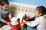 Education Preschool 4 year olds boy and girl playing with toy barn and small dolls