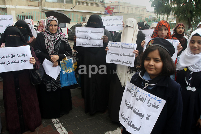 Palestinian teachers hold banners during a protest to demand their salaries, in front of the Ministry of Education in Gaza City December 14, 2014. Photo by Mohammed Asad