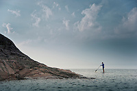 A female stand up paddler is dwarfed by the landscape while paddling on Lake Superior near Marquette Michigan.