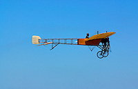 A replica of an antique French airplane flies through a clear blue sky