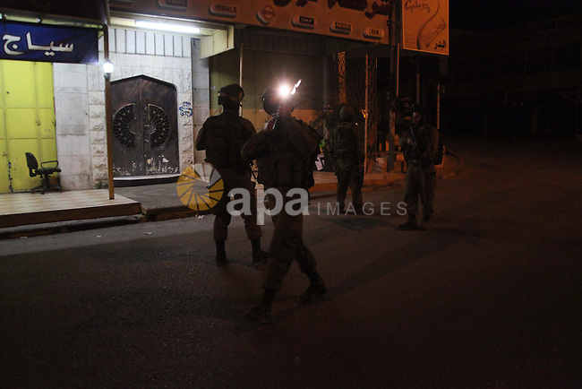 Israeli soldiers take part in an operation in a street of the West Bank town of Hebron on June 17, 2014 as Israeli forces broadened the search for three teenagers believed kidnapped by militants and imposed a tight closure of the town. Israeli Prime Minister Benjamin Netanyahu demanded Palestinian president Mahmud Abbas's help in securing the release of three kidnapped teenagers, as the army launched a massive crackdown on Islamist movement Hamas. Photo by Mamoun Wazwaz