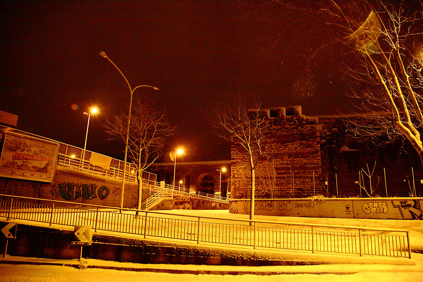 Rome, Pigneto: Urban view at the borders of the Pigneto quarter. There are ancient walls and arcs (this is the Felice aqueduct) on the background, and typical writings on the wall in foreground. It is a peculiar view, since it is taken in the very early morning after a snowing night (February, 2012).