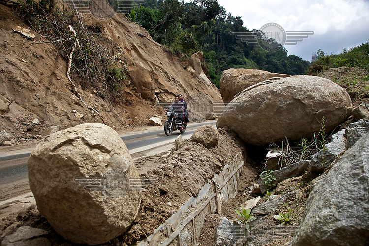 A couple, riding a motorbike on mountain road, pass several fallen boulders that came down in a rockslide. /Felix Features