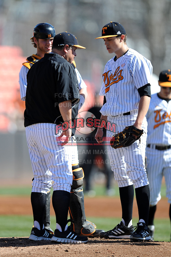 Tennessee Volunteers catcher David Houser #22 listens in as head coach Dave Serrano #12 talks with starting pitcher Kyle Serrano #11 during a game against the UNLV Runnin' Rebels at Lindsey Nelson Stadium on February 22, 2014 in Knoxville, Tennessee. The Volunteers defeated the Rebels 5-4. (Tony Farlow/Four Seam Images)