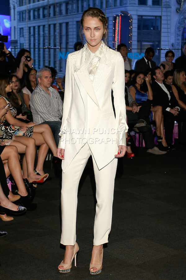 """Model walks runway in a white silk lace blouse with white lace blazer and white pants, from the Yuna Yang Spring Summer 2013 """"Close your eyes and see the world"""" collection, at the NASDAQ Marketsite, during New York Fashion Week, on September 7, 2012."""