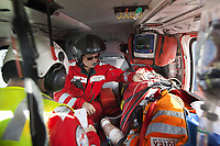 "Switzerland. Canton Ticino. Blenio valley. A Rega Agusta AW109 SP Grand ""Da Vinci"" helicopter flies to the nearest most suitable hospital after a rescue operation. The paramedic Giovanni Beldi (C) takes care of a badly injured man (R) while the doctor Damiano Salmina (L) takes notes on the patient's conditions. The patient, lying on a stretcher, is a worker from the Rotex company who was injured during a logging operation. All Rega helicopters carry a crew of three: a pilot, an emergency physician, and a paramedic who is also trained to assist the pilot for radio communication, navigation, terrain/object avoidance, and winch operations. The name Rega was created by combining letters from the name ""Swiss Air Rescue Guard"" as it was written in German (Schweizerische Rettungsflugwacht), French (Garde Aérienne Suisse de Sauvetage), and Italian (Guardia Aerea Svizzera di Soccorso). Rega is a private, non-profit air rescue service that provides emergency medical assistance in Switzerland. Rega mainly assists with mountain rescues, though it will also operate in other terrains when needed, most notably during life-threatening emergencies. As a non-profit foundation, Rega does not receive financial assistance from any government. The AgustaWestland AW109 is a lightweight, twin-engine, helicopter built by the Italian manufacturer Leonardo S.p.A. (formerly AgustaWestland, Leonardo-Finmeccanica and Finmeccanica). Leonardo S.p.A is an Italian global high-tech company and one of the key players in aerospace. In close collaboration with the manufacturer, the Da Vinci has been specially designed to cater for Rega's particular requirements as regards carrying out operations in the mountains. It optimally fulfills the high demands made of it in terms of flying characteristics, emergency medical equipment and maintenance. Safety, performance and space have been increased, and maintenance and noise emissions reduced. An intravenous therapy is a therapy that delivers liquid substance"