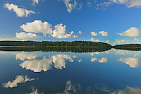 Cumulus clouds reflected in Lac Seul<br /> Ear Falls<br /> Ontario<br /> Canada