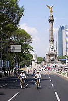 Cyclists and political protesters in front of the Angel Monument or Monumento a la Indendencia  on Paseo de la Reforma, Mexico City