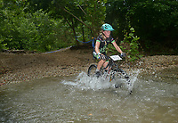 NWA Democrat-Gazette/BEN GOFF @NWABENGOFF<br /> Tai-Lee Smith, a category 3 women age 13-14 racer from Breckenridge, Colo., fords a creek Sunday, July 16, 2017, during cross country races on the final day of the 19th annual Fat Tire Festival at Lake Leatherwood City Park in Eureka Springs.