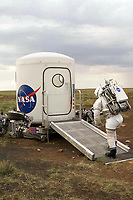 "JSC2006-E-39964 (4-15 Sept. 2006) --- Testing the next generation of spacesuits and equipment in the Arizona desert, an ""astronaut"" heads to a mock way station that has been delivered to the site by a giant robot capable of ""walking"" over steep terrain. The giant robot, known as Athlete or All-Terrain Hex-Legged Extra-Terrestrial Explorer vehicle, can be seen at rest beneath the way station. The test was part of the 2006 NASA's Desert Research and Technology Studies (RATS), a team of scientists and engineers who test futuristic equipment that may one day be used for explorations of the moon and Mars."