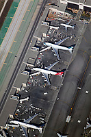 aerial photograph of loading and unloading of airliners at the international terminal or the Los Angeles International airport, LAX, Los Angeles, California. Aircraft on the ramp include Quantas Airways, Cathay Pacific and Singapore Airlines.