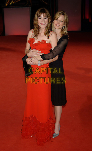 "JENNIFER CARPENTER & LAURA LINNEY.62nd International Film Festival,.At the premiere of ""The Exorcism of Emily Rose"".Venice, 1st September 2005.full length La Bienale red strappy gown dress black chiffon hug arms hugging.Ref: PL.www.capitalpictures.com.sales@capitalpictures.com.©Capital Pictures."