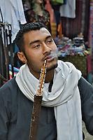 Egyptian man smoking waterpipe or hookah in bazaar, Luxor, Egypt.
