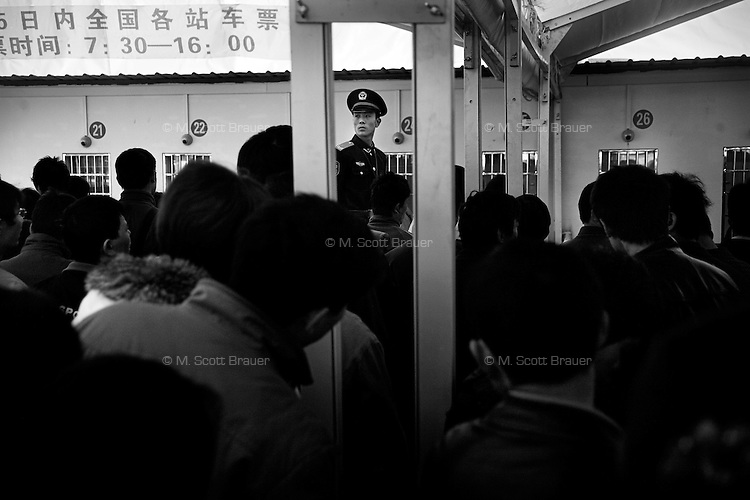 Military police (People's Armed Police) look over a crowd waiting to buy train tickets at the Kunming Railway Station for the Spring Festival peak travel period in Kunming, Yunnan Province, China.