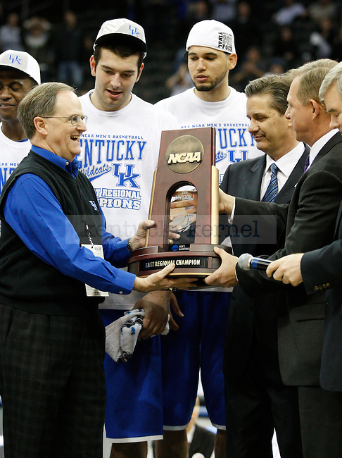 Lee T. Todd Jr. and John Calipari receive the trophy for winning the region after the Elite 8 game of the 2011 NCAA Basketball Tournament, at the Prudential Center, in Newark, NJ.  Photo by Latara Appleby | Staff
