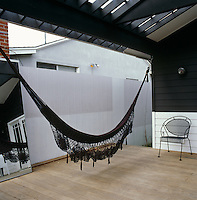 A black cotton hammock hanging on the porch