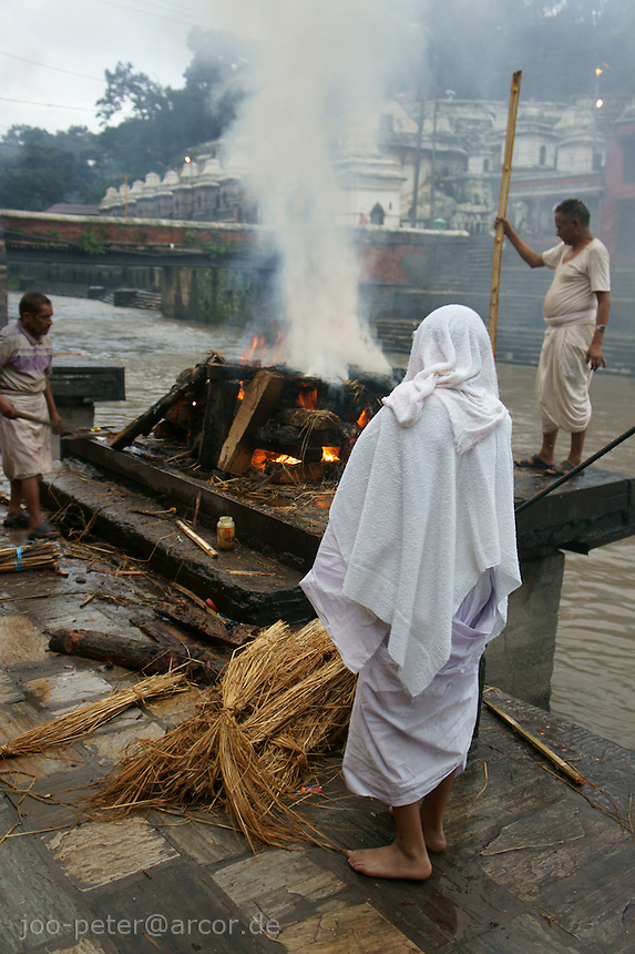 cremation at Ram Ghat , Basmati river, Pashupatinath, Kathmandu, Nepal, September 2011. White clothes symbolize mourning about death. Pashupatinath is Nepals most holy pilgrimage destination with many  temples and cremation area.