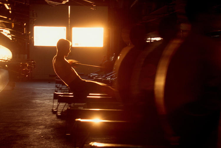 Rowing, Male rower working out in the boathouse on the erg, rowing machine, in winter sun,