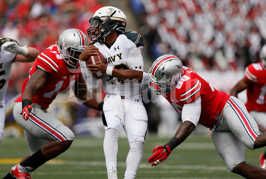 Navy Midshipmen quarterback Keenan Reynolds (19) is tackled by Ohio State Buckeyes linebacker Curtis Grant (14) and Ohio State Buckeyes defensive lineman Steve Miller (88) during Saturday's NCAA Division I football game at M&T Bank Stadium in Baltimore on August 30, 2014. (Dispatch Photo by Barbara J. Perenic)