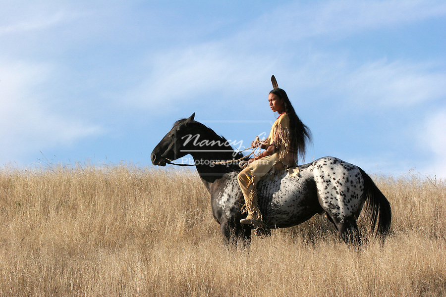 A teenage Native American Indian boy on horseback riding the prairie of South Dakota