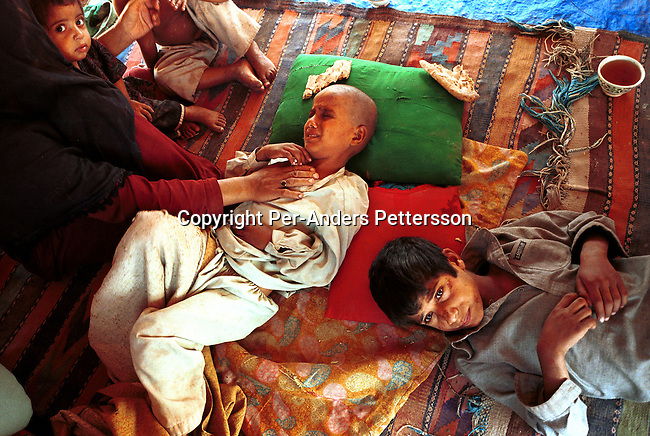 An unidentified newly arrived refugee family recently arrived from Afghanistan on October 6, 2001in New Shamshtoo, a camp run by UNHCR outside Peshawar in Pakistan. About 2 million Afghan refugee are in Pakistan who have arrived the last 20 years..Photo: Per-Anders Pettersson/ Grazia Neri.