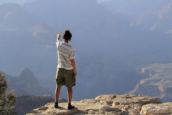 Man pointing in the distance while on the edge of the South Rim, Grand Canyon National Park, Arizona. . John offers private photo tours in Grand Canyon National Park and throughout Arizona, Utah and Colorado. Year-round.