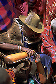 Lolgorian, Kenya. Siria Maasai chief pouring milk from one gourd to another. Cucurbitaceae; Lagenaria siceraria.