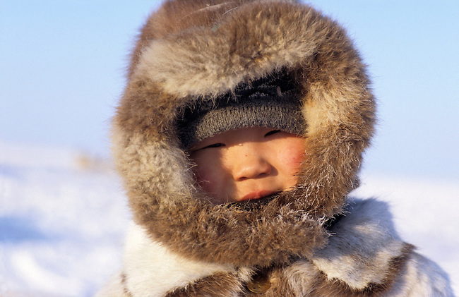 Dolgan boy at a reindeer herders' camp, dressed in traditional furs. Taymyr, Northern Siberia, Russia