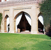 The loggia houses a sitting and dining area concealed behind the curtains
