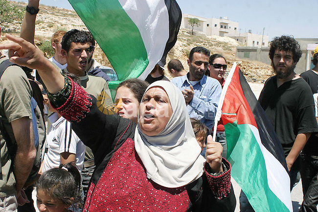 Palestinian protesters hold Palestinian flag during a demonstration against the construction of Israel's separation barrier  in the West Bank village of Maasarah near Bethlehem, Friday,June 5, 2009. Photo Najeh Hashlamoun