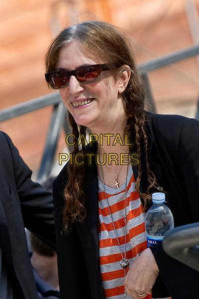 Patti Smith.attends 2012 Giffoni Film Festival, Giffoni Valle Piana, Italy. .July 19th, 2012.half length black jacket white orange striped stripes top sunglasses shades hair braids plaits bottle water.CAP/IPP.©IPP/Capital Pictures.
