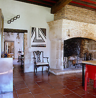 The dining room has a vast stone fireplace and terracotta tiled floor and is decorated with pieces of modern art