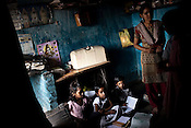 Young children attend tution classes in a small house. Residents near the coal mine talk of problems of dust and pollution in Kujama Basti, in Dhanbad, Jharkhand, India. Photo: Sanjit Das