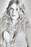 Close up of a young female with long curly blonde hair and blue eyes wearing pearl necklace looking at camera
