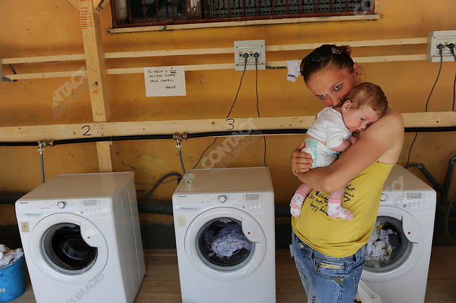 In the camp of piazza d'Armi in L'Aquila, where 1,300 people who lost their homes in the Abruzzo earthquake in April are now living in tents, Anca Costin waited at one of the laundry points with her two month old daughter Alessia. May 22, 2009