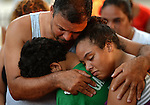 Gilberto Ortiz, step-father to Grisel Sanchez, holds two of Sanchez's three children, Isaiah Vasquez, 11, and Idalys Vasquez, 13, during a vigil for Grisel Sanchez, 31, in Boston on Wednesday, July 29, 2015. According to Boston Police, Sanchez was killed by a strayed the night before in Puddingstone Park at the corner of Seaver and Normandy Streets in Boston. Photo by Christopher Evans