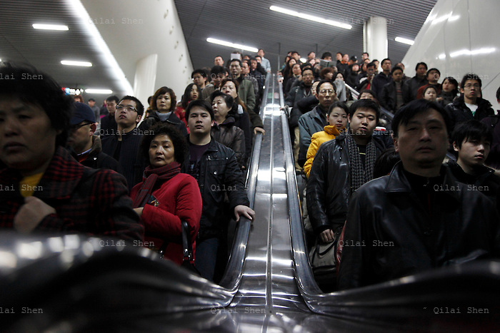 Morning commuters crowd onto escalators in the People's Square subway station in Shanghai, China on 25 February 2009.  Shanghai's subway system, with a total annual passenger flow of over 700 million, is the world's 10th largest transportation network in traffic. The city is also quickly expanding it's subway system, to accommodate a swelling population of over 23 million residents according to the latest census in 2010.