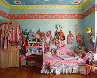 A riotously colourful girl's bedroom with a collection of hats, toys and bags hanging on the wall