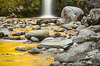 Dorothy Falls near Hokitika with golden light of sunset reflecting in water, West Coast, South Westland, New Zealand