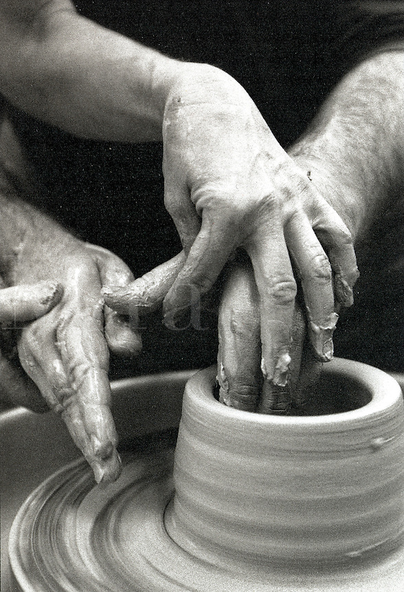 Hands of pottery instructor helping student with spinning clay on pottery wheel.