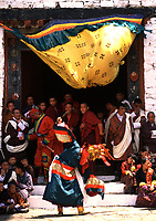 Asia, Buthan, Paro Dzong, Tshechu festival, young dancer dancer with clown jokeing with smiling monks in backround, Bhutan