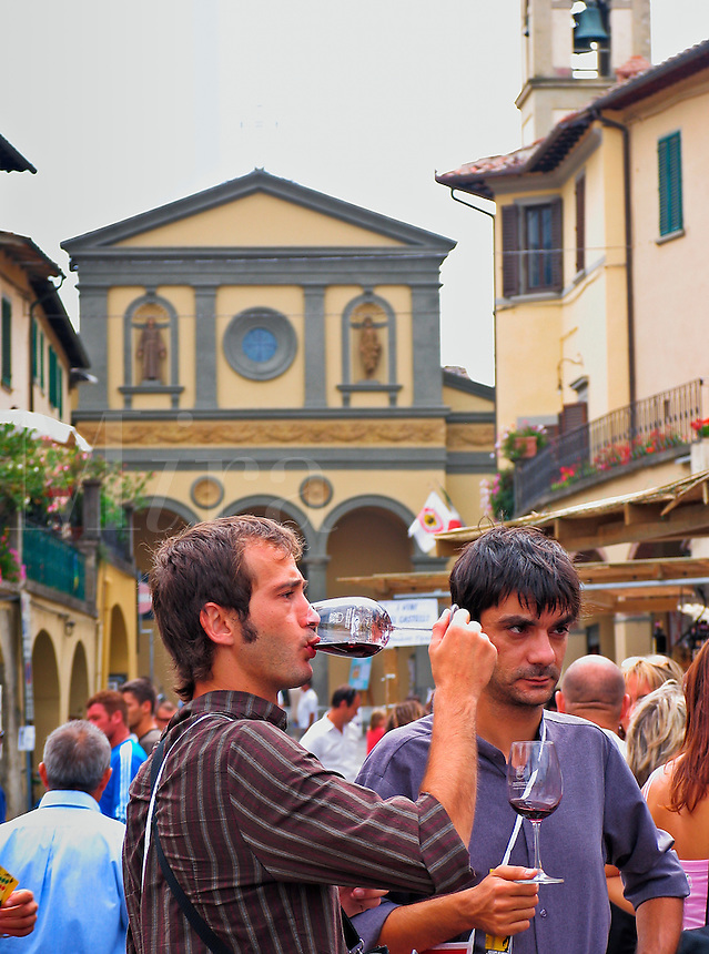 Greve in Chianti, Italy, two men in piazza crowded with people sample wine during wine festival weekend - no model release availabl
