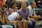 Sasha Obama rests her head on her legs as her dad, United States President Barack Obama, first lady Michelle Obama and sister Malia Obama attend the Hawaiian Airlines Diamond Head Classic men's basketball game between the Oregon State Beavers and the University of Akron Zips at the University of Hawaii at Manoa Stan Sheriff Center, Sunday, December 22, 2013. The first lady's brother, Craig Robinson, is the Oregon State University Men's Head Basketball Coach.  At far right is Bobby Titcomb, one of the President's oldest friends.<br /> Credit: Cory Lum / Pool via CNP