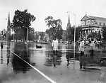 Waterbury's Exchange Place was covered with several inches of water. Note the oil drums floating by and the stalled car in the distance. Police officers Paul Guglielmo (center) and Frank Roberts held up west-bound traffic.