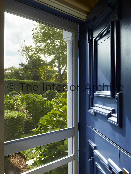 The front entrance is a blue painted stable door and has a wooden screen covering the doorway.