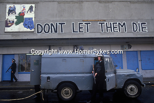 Northern Ireland The Troubles. 1980s. 1981 Catholic political mural wall painting depicting the plight of the H Block Hunger Strikers and sign saying Dont Let Them Die. Armed RUC Royal Ulster Constabulary police officers looking for rioters.