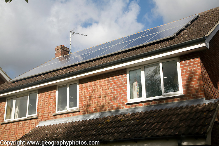 Large array of solar panels on domestic house roof
