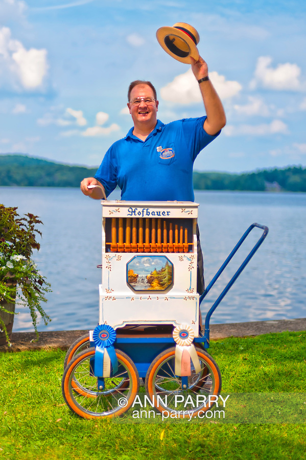 Aug. 25, 2012 - Middlebury, Connecticut, U.S. -- DAN WILKE, Organ Grinder from Buffalo NY, who is a member of Carousel Organ Association of America, raises his straw hat in welcome as he plays music along Lake Quassapaug, during CAOO's Organ Rally at Quassy Amusement Park.